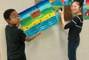 two students hanging art work in the hallway