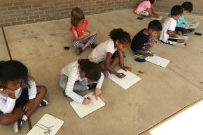 students on sidewalk drawing nature