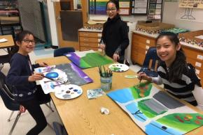 three students painting